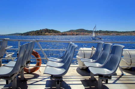 Saint-Tropez, Provence, France - August 21 2016: Seats on a passenger ferry from St Raphael to St Tropez, with a sailing boat on the blue Mediterranean Sea in the distance