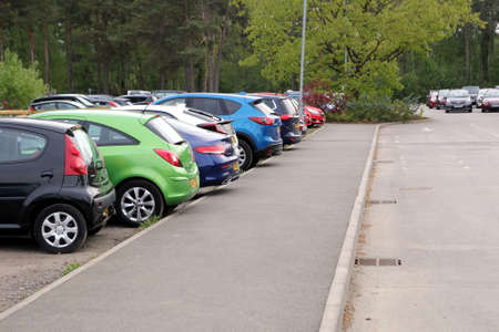 Wisley, Surrey, UK - April 30 2017: Car park or parking lot with colorful different coloured cars, trees in distance