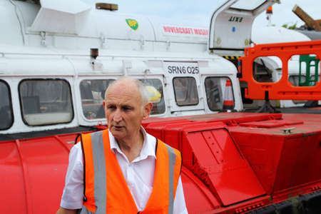 aéroglisseur: Lee-on-the-Solent, Hampshire, UK - June 10 2017: Volunteer at the Hovercraft Museum in England talking to visitors about the SR.N6 hovercraft behind him Éditoriale