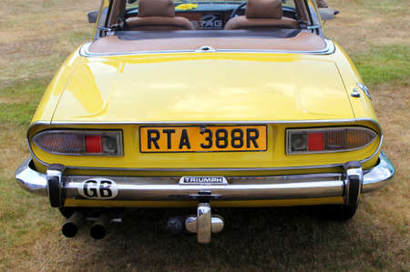 Sandhurst, Surrey, UK - June 18th 2017: Rear view of a yellow Triumph Stag convertible sports car at an auto fair