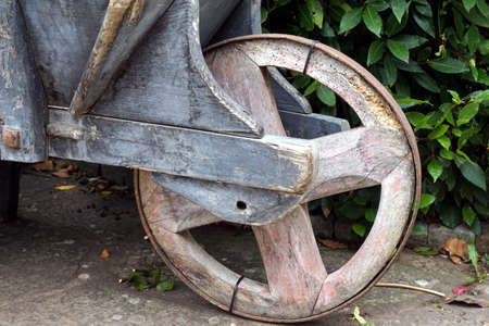 Rustic wooden wheelbarrow wheel, on stone track with leaves in background