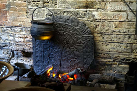 Traditional old antique pots and pans over a log fire with ornate cracked cast iron fire back against a stone wall 版權商用圖片