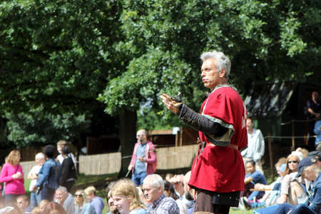 Warwick, UK - July 22 2017: Medieval re-enactor in traditional Tudor clothes addresses visitors to Warwick Castle Editorial