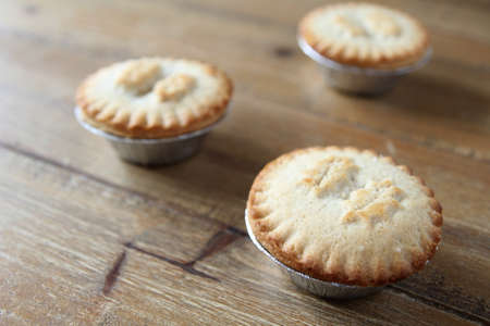 Close up shot of three mince pies in foil cases, traditional Christmas dessert Stock Photo