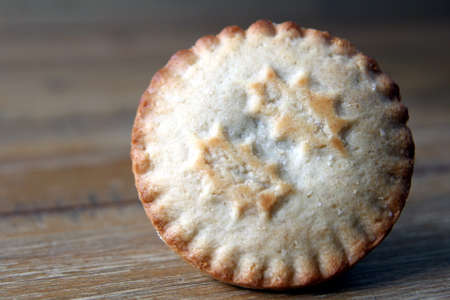 Close up of a mince pie, a traditional Christmas dessert, on a wooden table Stock Photo