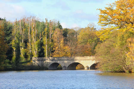 Stone bridge over a lake in the Autumn sunshine with tree leaves turned orange and yellow in the fall