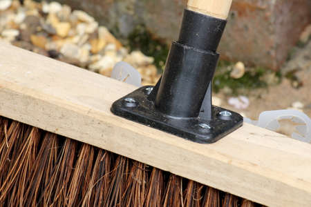 Close up of a garden broom or yard brush where the handle meets the head
