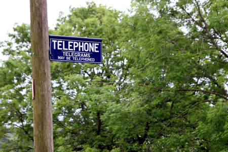 Dorset, UK - May 31st 2016: Vintage British telephone and telegram sign on a traditional wooden pole.