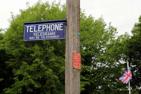 Dorset, UK - May 31st 2016: Vintage British telephone telegraph and telegram signs on a traditional wooden pole.