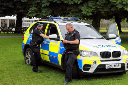 Beaulieu, Hampshire, UK - May 29 2017: Two British policemen taking a break with their BMW patrol car