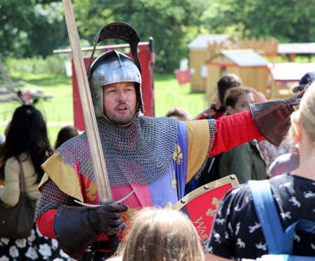 Warwick, UK - July 22 2017: Medieval knight re-enactor on horseback with sword, directing visitors at Warwick Castle Editorial