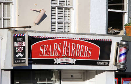 Lymington, Hampshire, UK - December 28 2017: Exterior of a traditional English barber shop, Sears Barbers, with traditional revolving red and white sign Redakční