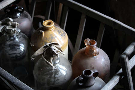 Dusty, rustic old glass demijohns or wine bottles in a wooden rack.