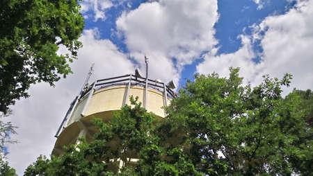 青空と雲の木々の間に、携帯電話のマストを備えたウォータータワー。
