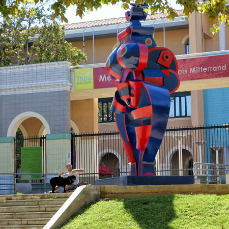 Sete, Herault, France  - Aug 21 2017: Man with his dog on the steps of the Mediatheque Francois Mitterrand  in Sete, Languedoc, France, next to the statue Standing Woman (renovated 2016)  by Joseph Szabo (1925-2010)