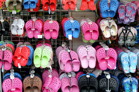 Valras-Plage, Herault, France - Aug 25 2017: Rack with lots of pairs of childrens soft rubber sandals or Crocs in various pink, blue, green and black colours