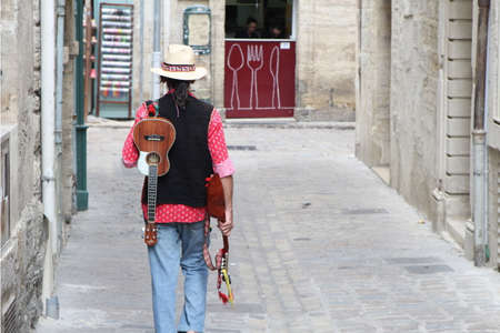 Pezenas, Herault, France - Aug 26 2017: Musician wearing a straw fedora hat, carrying a mandolin and ukelele, walking down a cobbled street towards a small cafe Editorial
