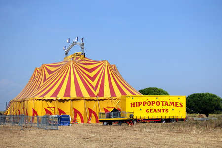 Valras-Plage, Herault, France - Aug 23 2017: Colourful red and yellow Circus Big Top in France, plus a trailer carrying a Giant Hippopotamus