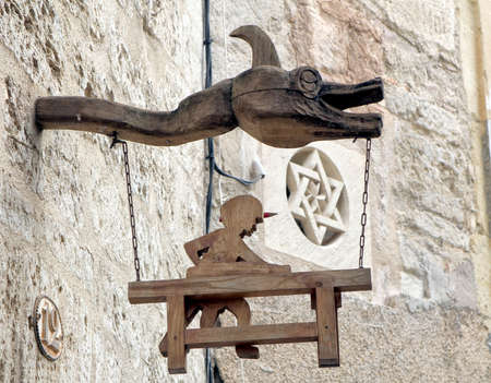 Pezenas, Herault, France - Aug 26 2017: Wooden creature head with a wooden sign depicting a woodworker, with in the backgrond a carved stone Star of David, in the Jewish quarter of Pezenas, Languedoc, France Editorial