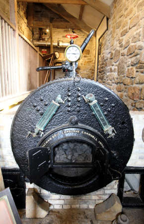 Cornwall, UK - April 8 2018: Coal fired boiler in a tin mine pumping station, with pressure gauge.
