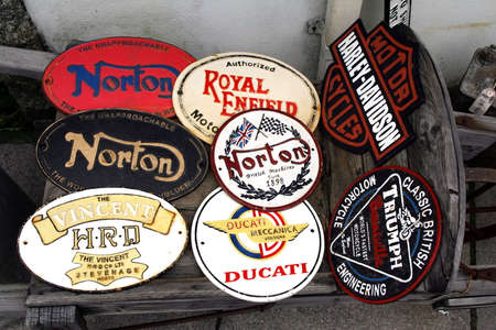 Tintagel, Cornwall, UK - April 10 2018: Enamel plaques or name plates with names of legendary classic motorcycle manufacturers such as Norton, Triumph, Vincent, Harley Davidson, Ducatti, Royal Enfield.
