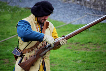 Falmouth, Cornwall, UK - April 12 2018: Historical military re-enactor dressed in bleu and yellow Tudor clothes with leather equipment demonstrating a working musket. Editorial