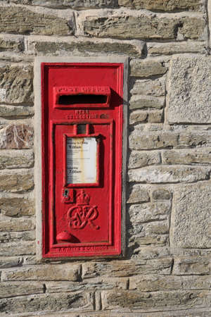 Porth, Cornwall, UK - April 7 2018: ~Red British Royal Mail post box set into a stone wall, bearing the initials GR meaning King George.