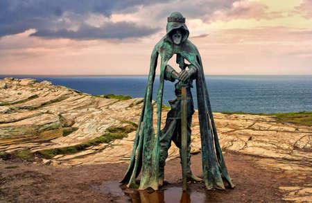 Tintagel, Cornwall, UK - April 10 2018: The King Arthur statue Gallos by Rubin Eynon stands on a rocky headland on the Atlantic coast of Cornwall.