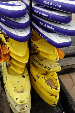 St Ives, Cornwall, UK - April 13 2018: Stacks of purple and yellow kayaks belonging to St Ives Kayak Hire, ready to be rented.