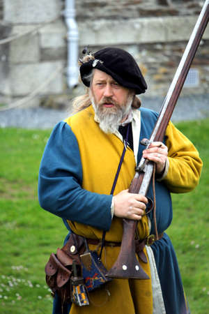 Falmouth, Cornwall, UK - April 12 2018: Historical military re-enactor dressed in bleu and yellow Tudor clothes with leather equipment with a working musket Editorial