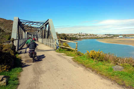 Camel Estuary, Cornwall, UK - April 11th 2018: Cyclists on the disused iron railway bridge on the Camel Trail in Cornwall