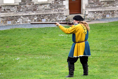 Falmouth, Cornwall, UK - April 12 2018: Historical military re-enactor dressed in bleu and yellow Tudor clothes firing a genuine 15th century firearm at a cabbage Editoriali