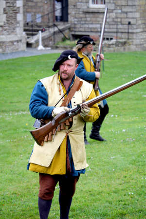 Falmouth, Cornwall, UK - April 12 2018: Historical military re-enactor dressed in bleu and yellow Tudor clothes with leather equipment with a working musket Sajtókép