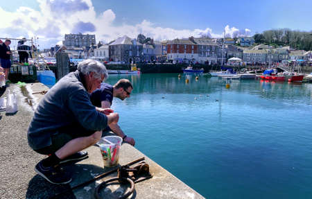 Padstow, Cornwall, April 11th 2018: Two men fishing or crabbing on the harbour wall in the Cornish seaside town of Padstow Editoriali