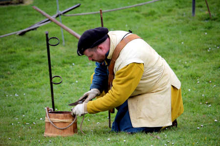 Falmouth, Cornwall, UK - April 12 2018: Historical military re-enactor dressed in bleu and yellow Tudor clothes with leather equipment loading a working musket Editoriali