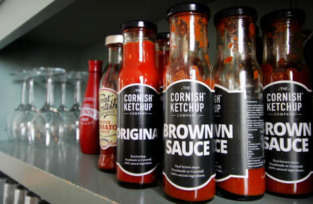 Falmouth, Cornwall, UK - April 12 2018: A selection of ketchups and sauces on an antique dresser in a cafe, featuring the Cornish Ketchup Company