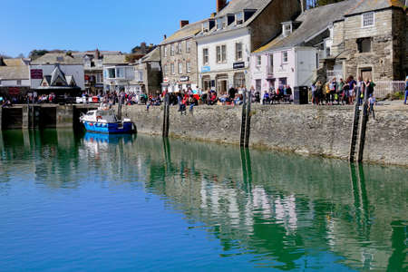 Padstow, Cornwall, April 11th 2018: Tourists, vacationers and holiday makers fishing and enjoying the sunshine on the harbour wall in the Cornish seaside town of Padstow