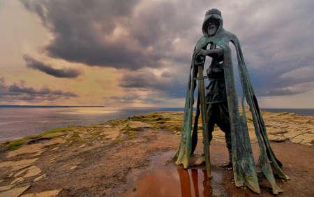 Tintagel, Cornwall, UK - April 10 2018: The King Arthur statue Gallos by Rubin Eynon stands on a rocky headland on the Atlantic coast of Cornwall