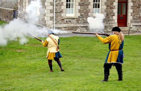 Falmouth, Cornwall, UK - April 12 2018: Historical military re-enactors dressed in blue and yellow Tudor clothes firing genuine 15th century firearms Editoriali