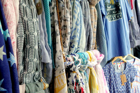 Padstow, Cornwall, April 11th 2018: Selection of different colored ladies scarves and tops, mostly blue and grey, for sale in a ladieswear fashion store Editoriali