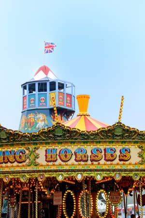 Guildford, England - May 28 2018: Old fashioned helter skelter fairground attraction, beyond a  vintage merry-go-round or carousel
