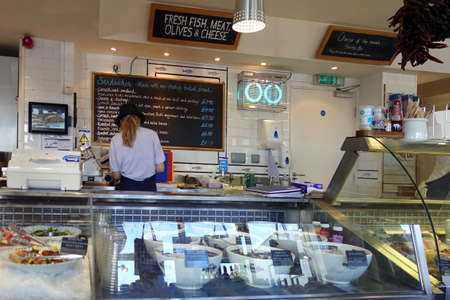 Padstow, Cornwall, April 11th 2018: Woman preparing food in a seafood speciality delicatessen Editoriali