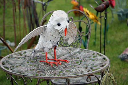 Guildford, England - May 28 2018: Unusual steel metalwork sculpture of a white owl on a wrought iron table
