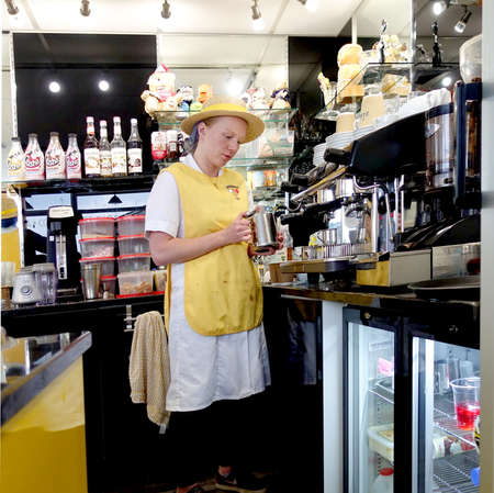 Padstow, Cornwall, April 11th 2018: Young female girl barista frothing the milk for a cappuccino in a coffee shop Sajtókép