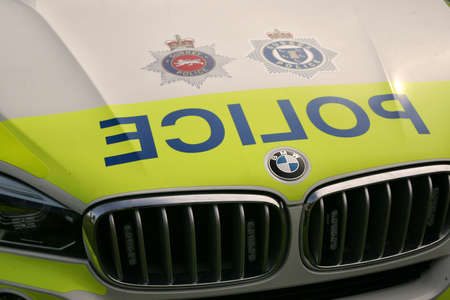 Guildford, England - May 28 2018: Close up of the front grille and bage of a BMW car beloning to Surrey and Sussex Police with the word POLICE reversed