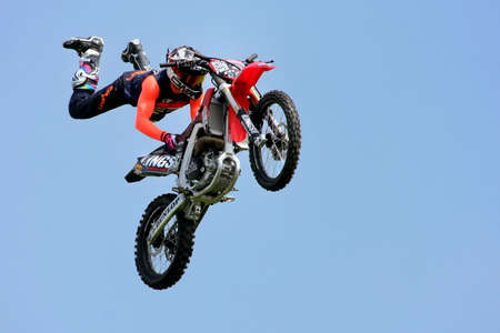 Guildford, England - May 28 2018: Stunt daredevil motorcycle rider, from the Bolddog Lings Freestyle Display Stunt Team, performing a trick in mid air