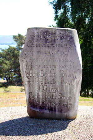 Brownsea, Dorset, England - June 02 2018: Stone commemorating the first Boy Scout camp held by Lord Baden Powell