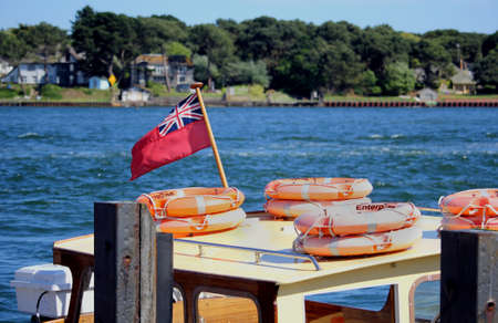 Sandbanks, Dorset, England - June 02 2018: The red Civil Ensign flying on the cabin roof of a leisure boat, along with some lifebelts, in Poole Harbour on a sunny day