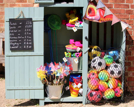 Brownsea, Dorset, England - June 02 2018: Wooden shed containing numerous colorful beach toys and games for sale to children Sajtókép