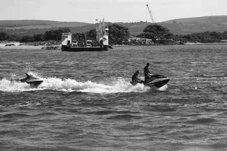 Sandbanks, Dorset, England - June 02 2018: Black and white shot of a jet ski crossing Poole Harbour in Dorset, with the chain link ferry in the background Editoriali